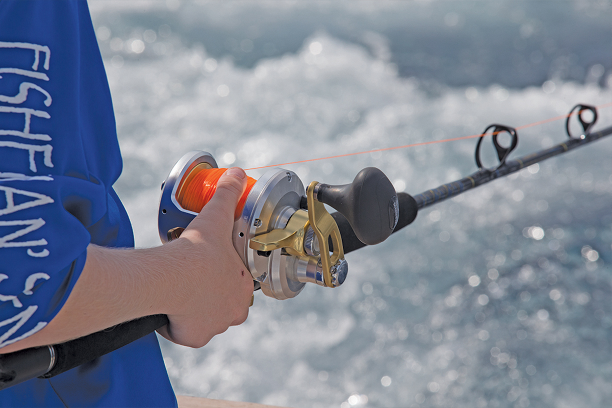 close up of child holding rod and reel