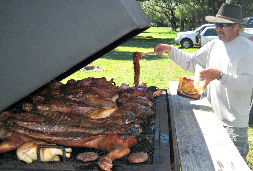 captain travis butters cooking pigs on a big grill for the captain of the year awards party