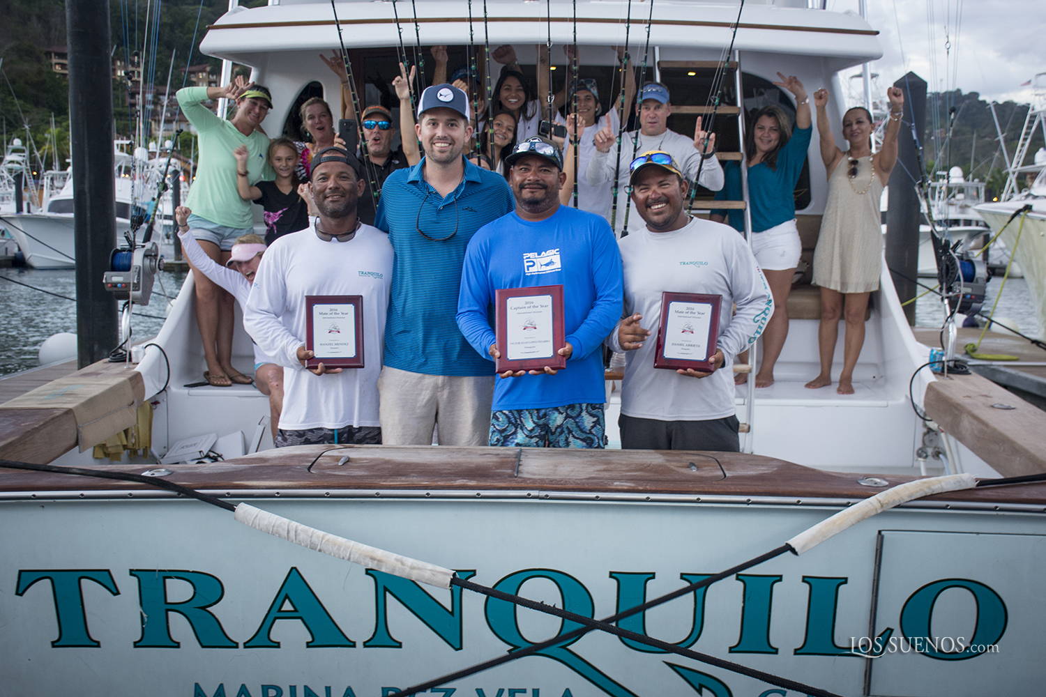 boat Tranquilo crew holding Captain of the Year plaques in the back of the boat