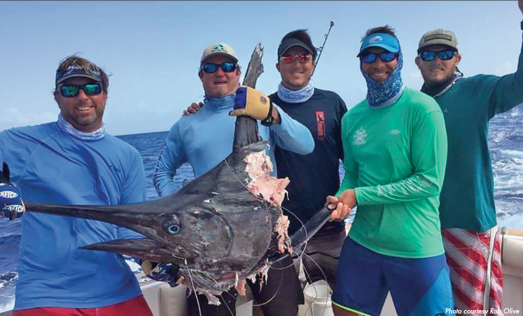 guys holding a shark bitten blue marlin
