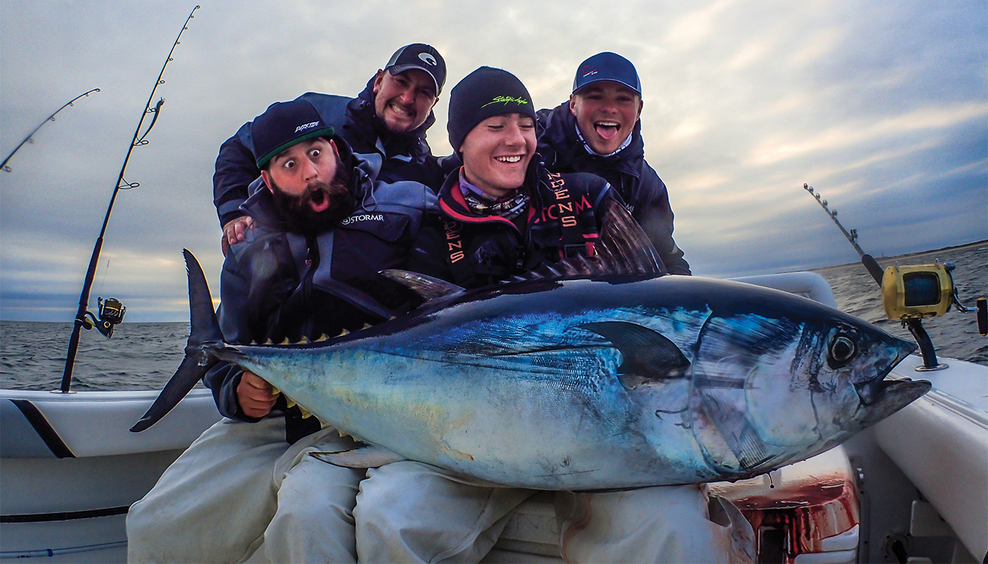 guys holding a tuna on back of boat