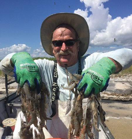Charles Perry holding shrimp up in his hands