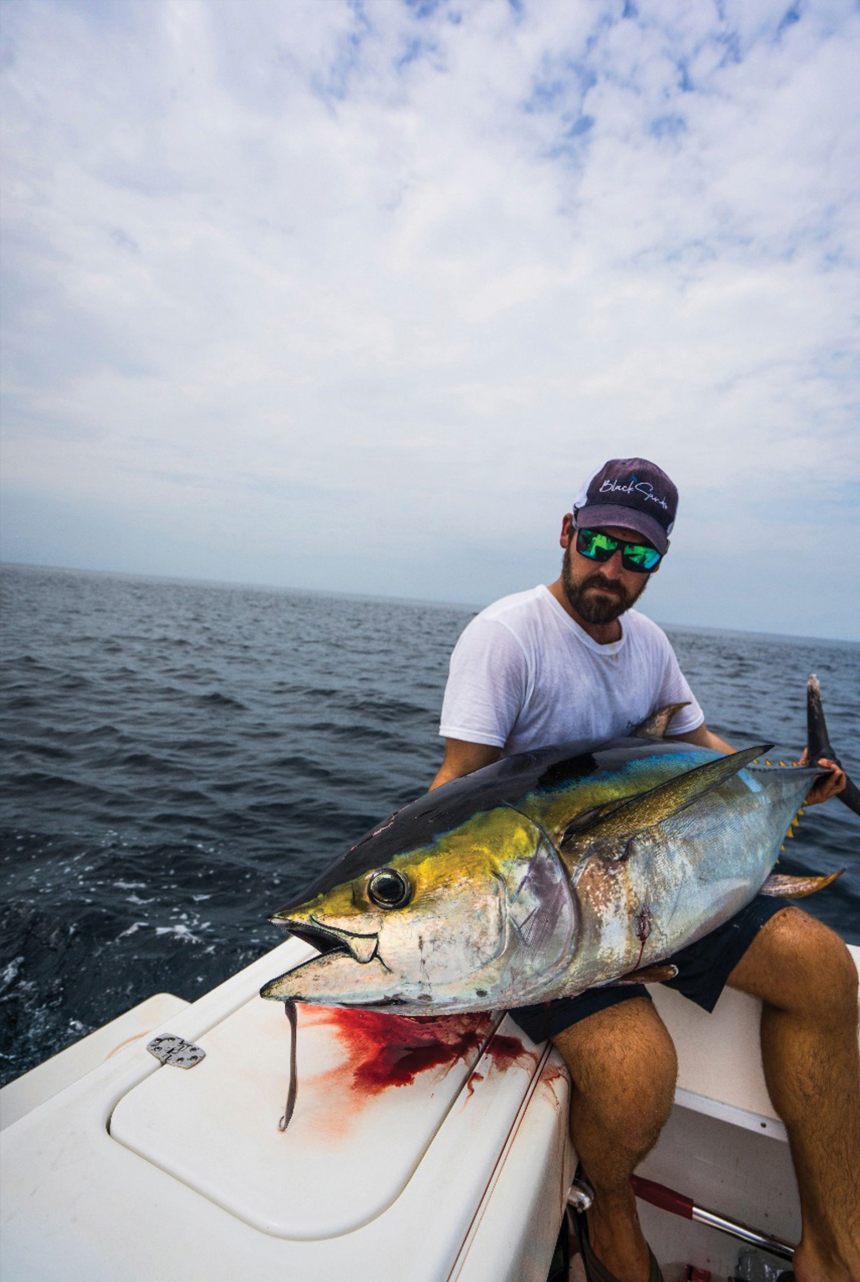 a fisherman holding a nice yellowfin tuna