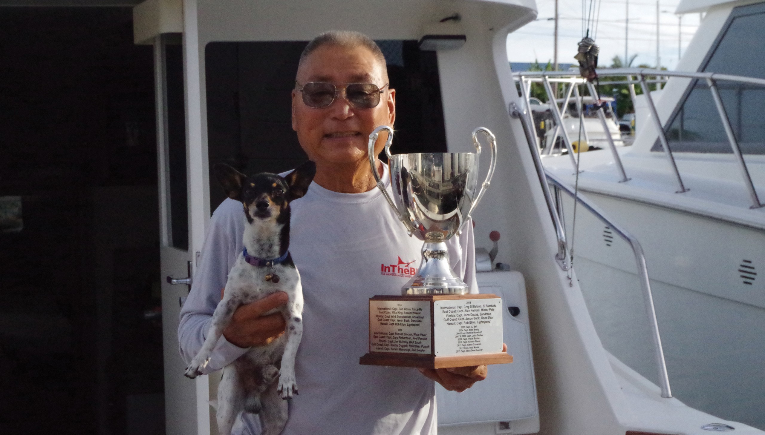 Captain Kerwin Maunaga holding a trophy in his left hand and a small dog in his right hand