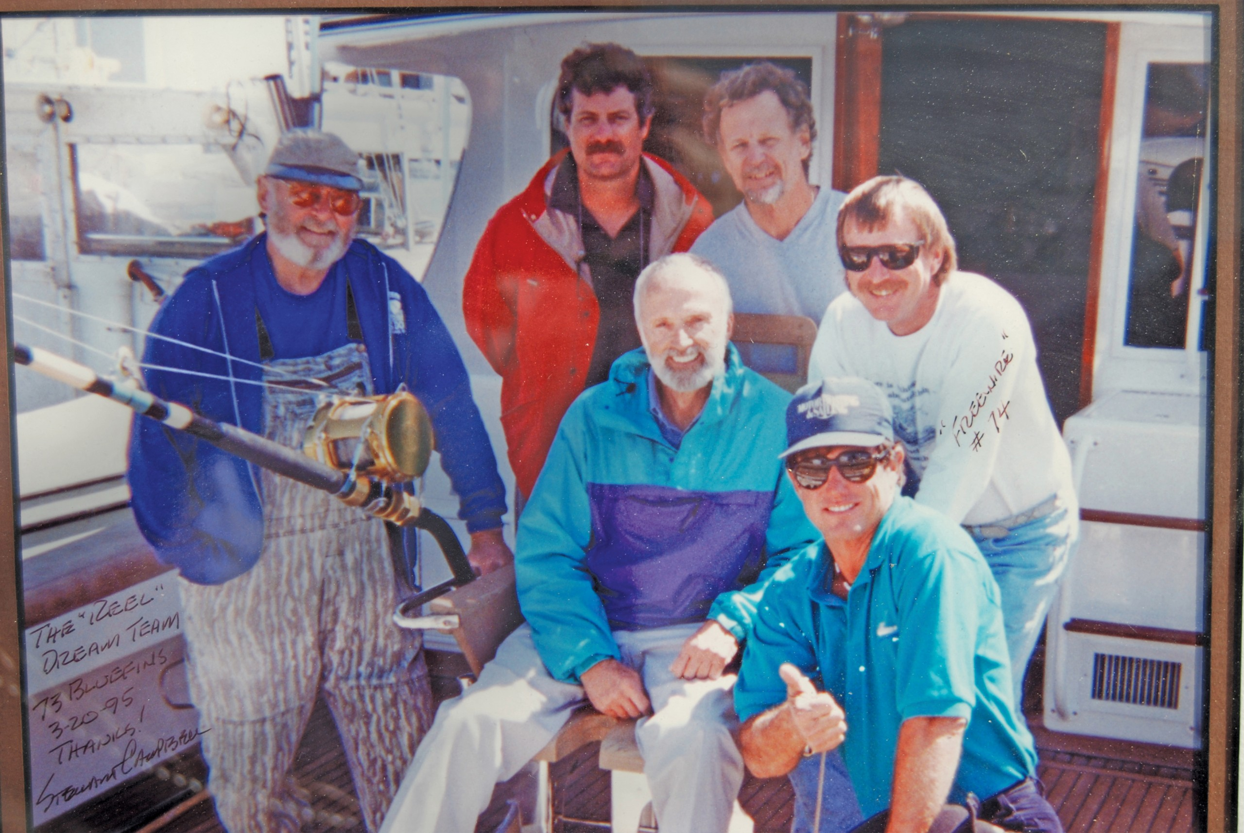 group of men in back of boat standing for a photo