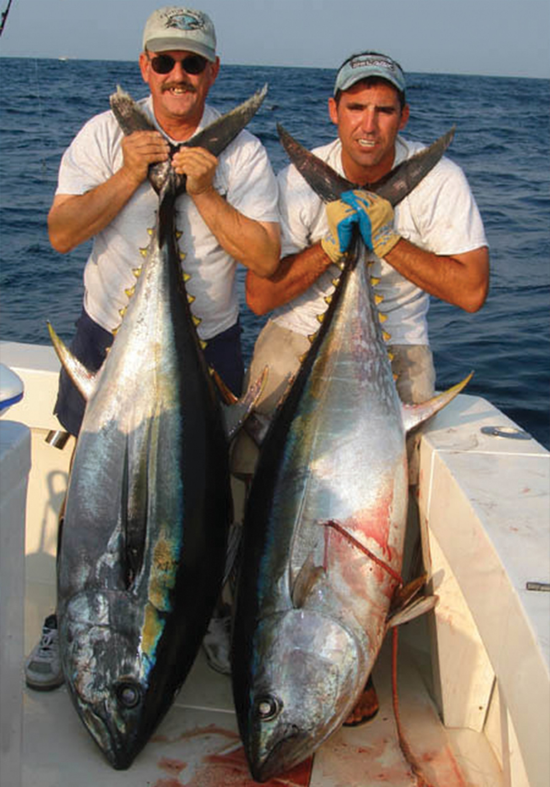 two guys on deck each holding a yellowfin tuna
