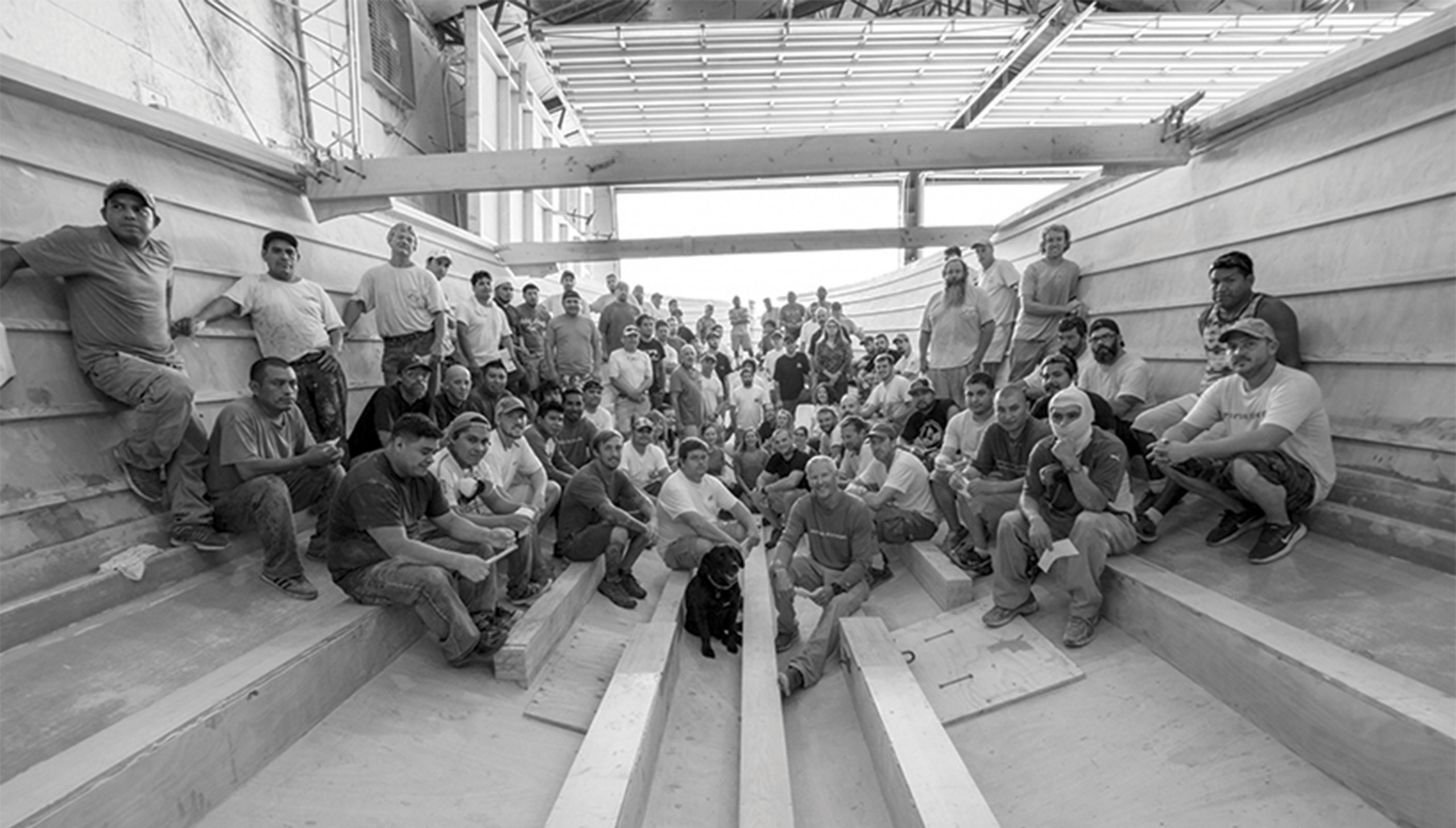 Black and white image of Bayliss Boatworks workers posing for a picture inside a hull
