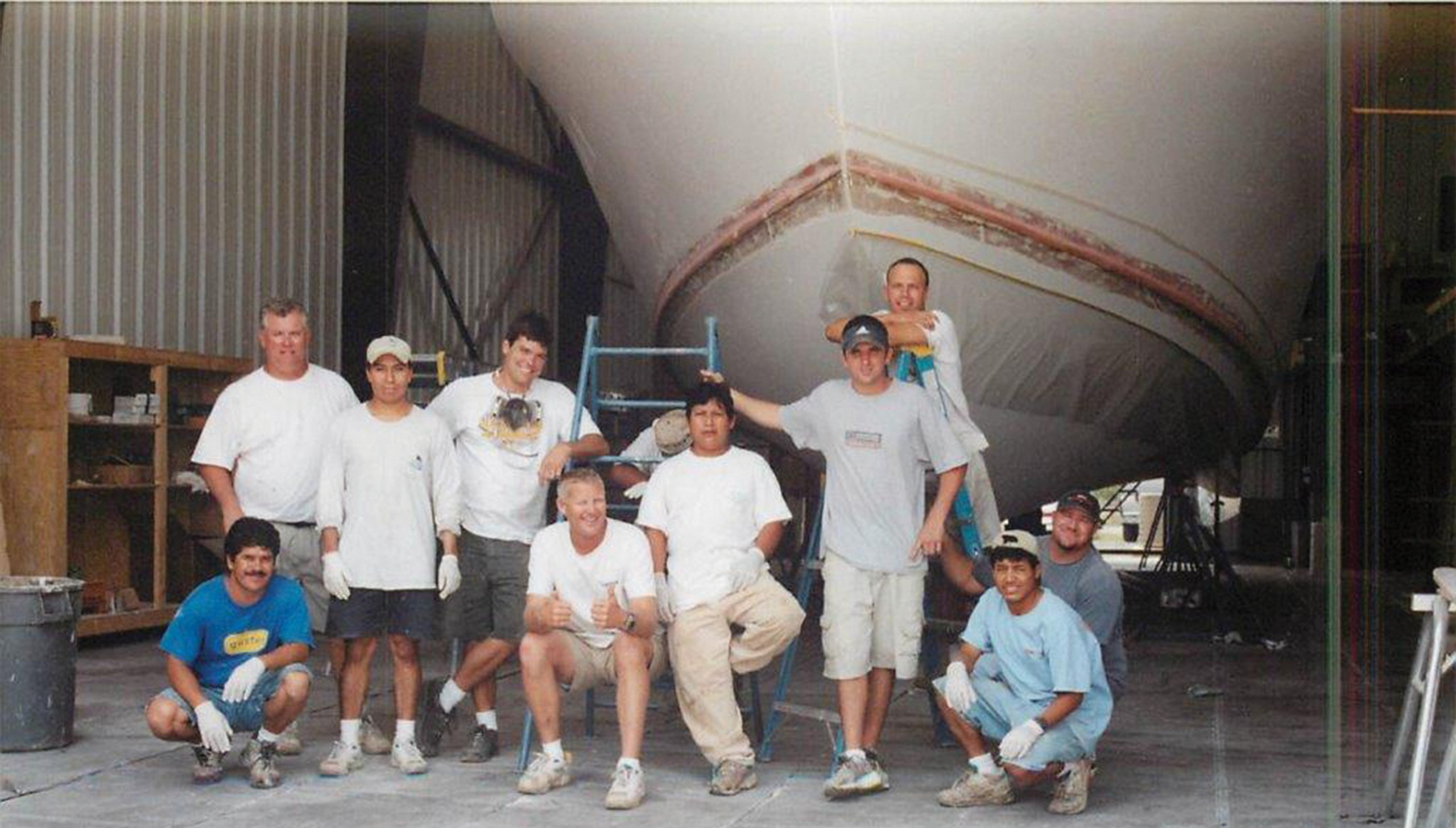 Bayliss Boatworks workers stopping work for a picture in front of a boat bow in a build shed