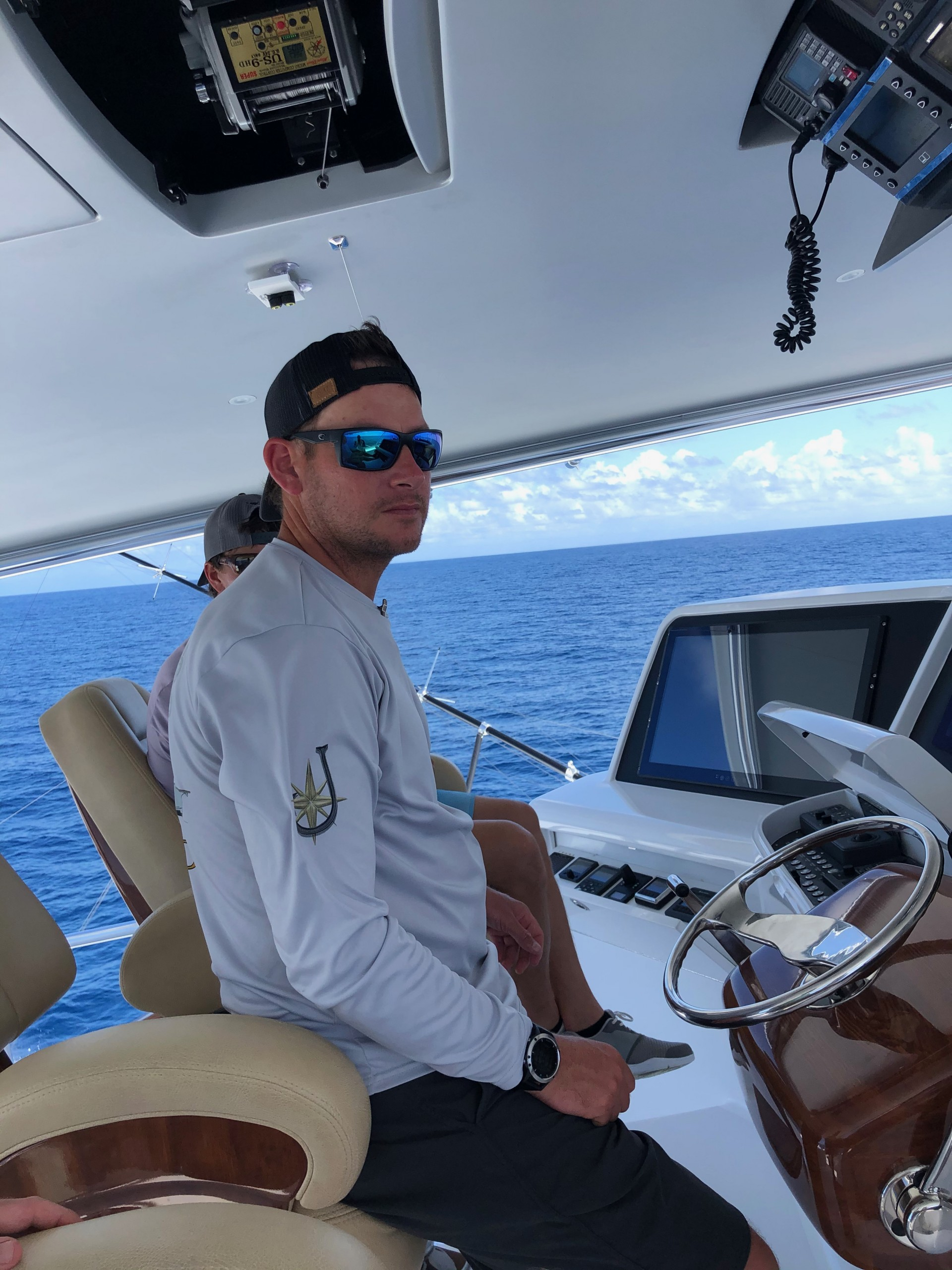 Jaruco Captain Jimmy Brown looking out on ocean from the bridge helm