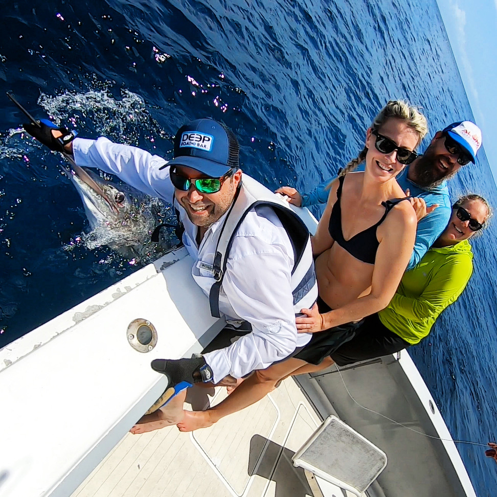 people in back of boat with a mate holding the bill of a striped marlin