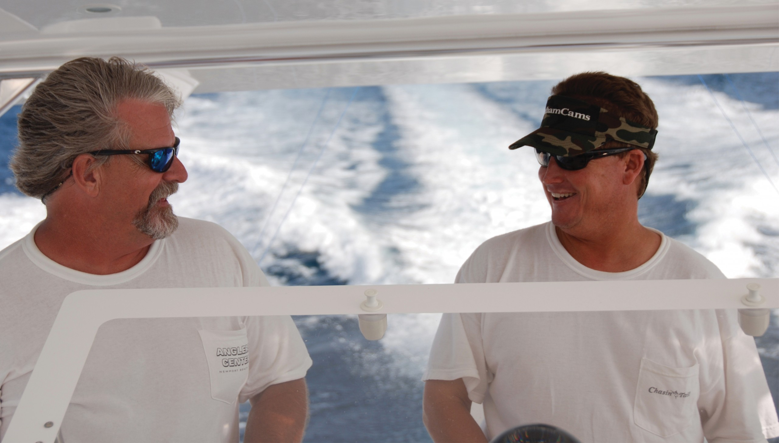twos guys looking at each other in the bridge of a sportfishing boat