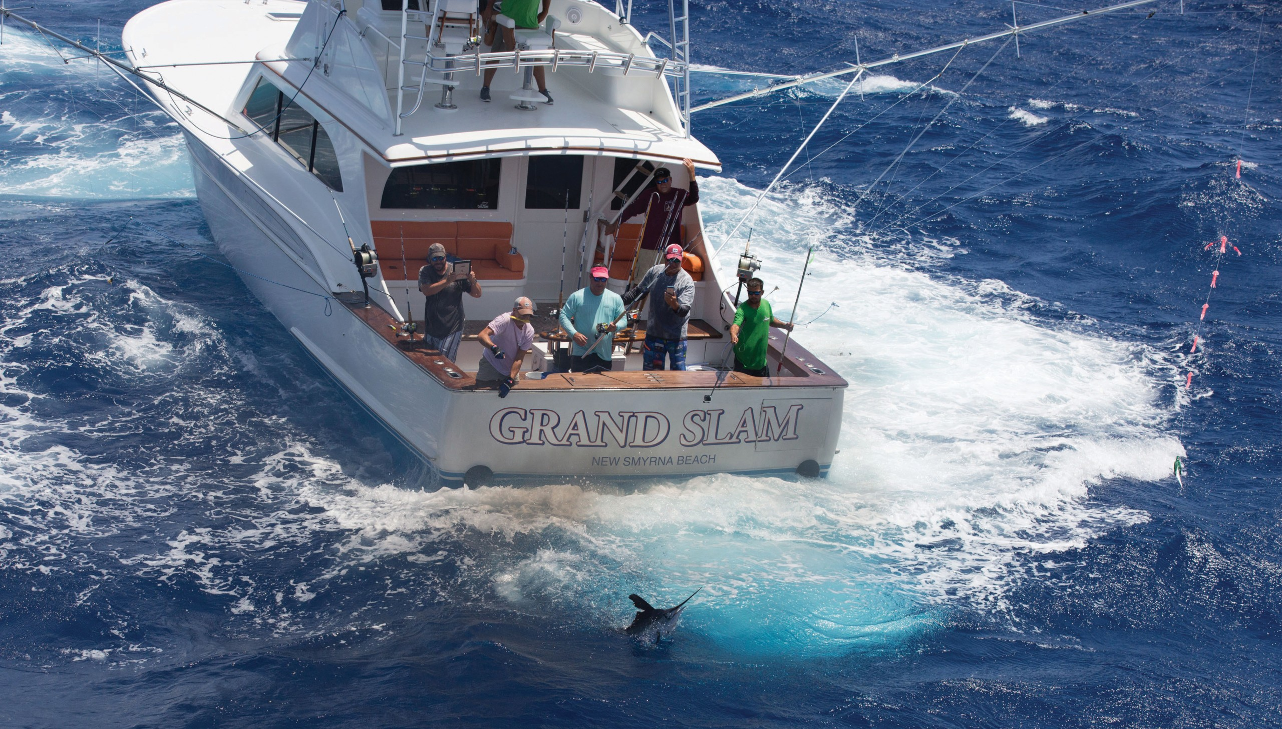 a boat backing down with a blue marlin jumping behind it