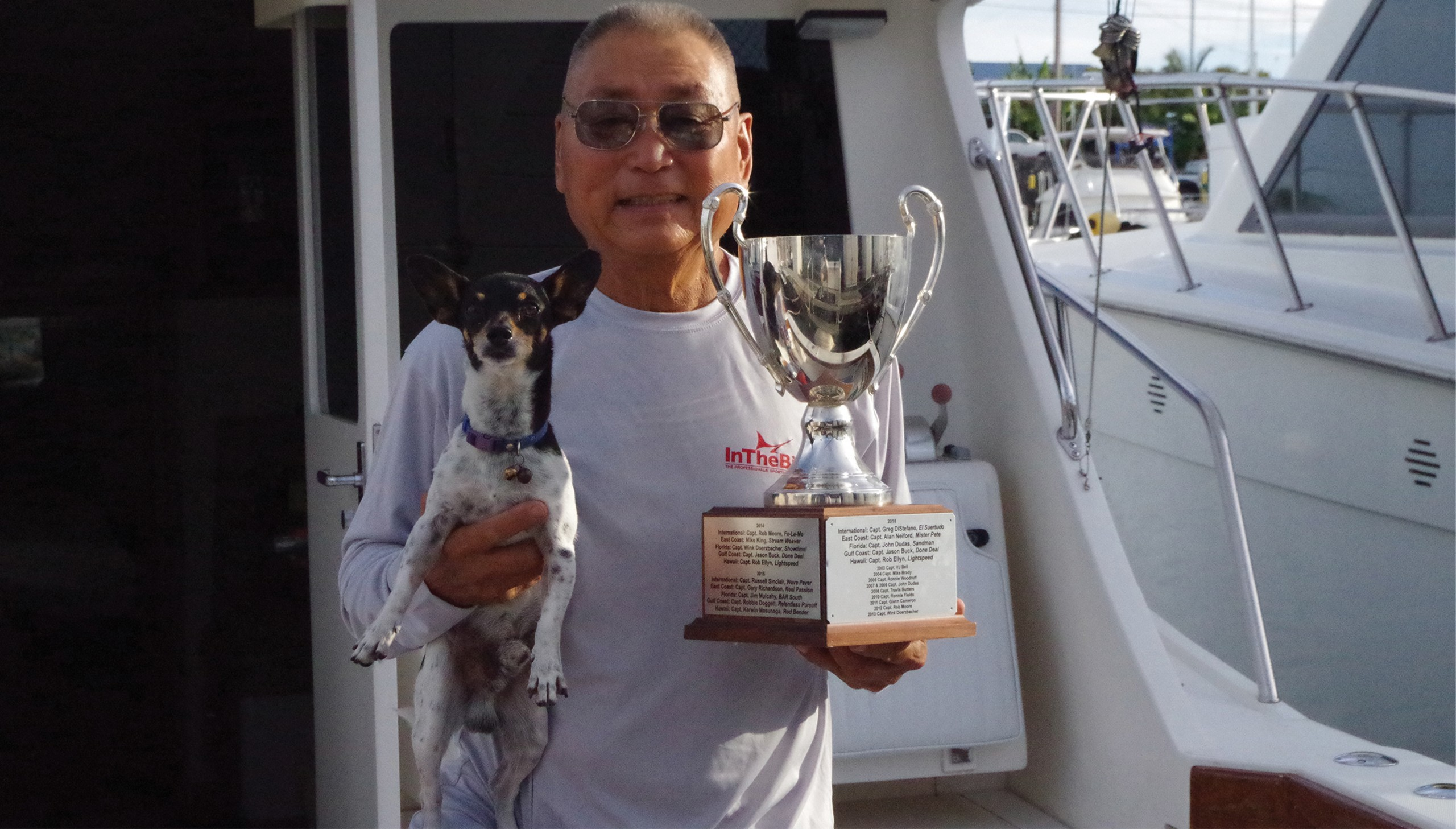 Picture of Kerwin Masunaga holding his dog and a trophy