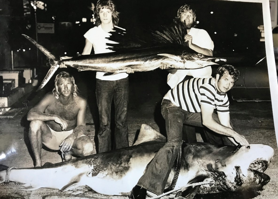 black and white picture of guys holding fish