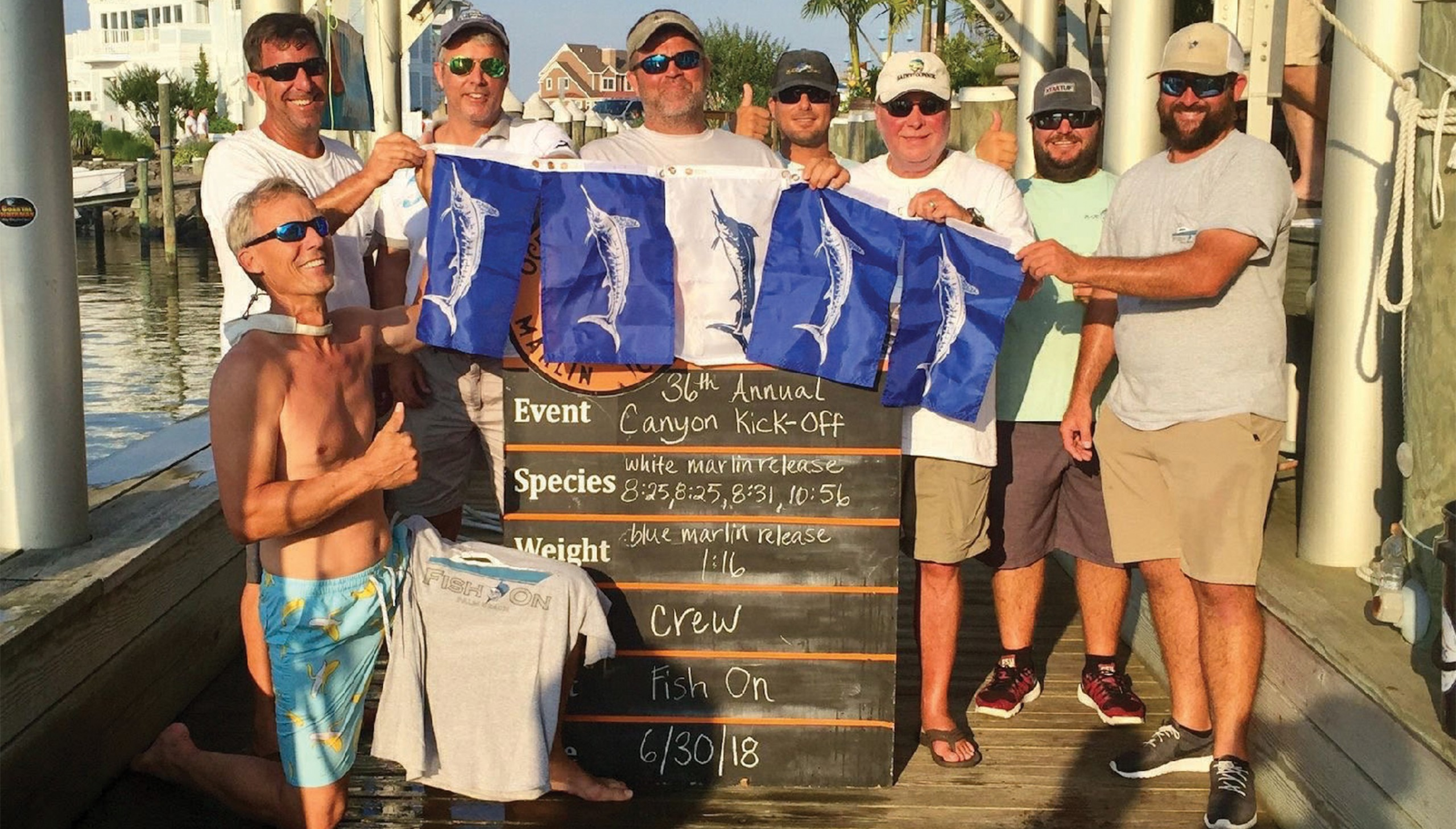 several guys returning from a fishing trip holding up billfish flags