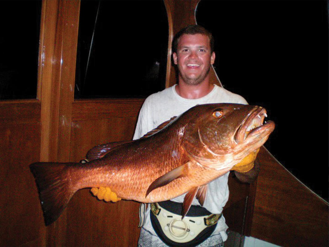 A guy holding a cubera snapper
