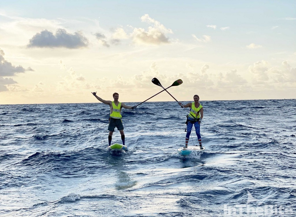 two paddle boarders with oars crossed